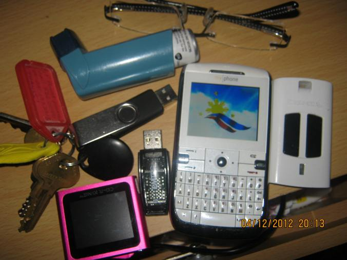 contents of Your Loyal Blogger's pocket, note the patriotic screensaver on China-made celfone :) neatness optional.