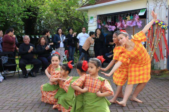 a rousing Filipiniana dance interpreted by children of Pinoy migrants including 7-year old Ella Cabauatan.  Seen in the background are H.E. Ambassador Virginia Benavidez, Consul Arlene Gonzales-Macaisa and Emb Finance Officer Rosalyn Del Valle-Fajardo